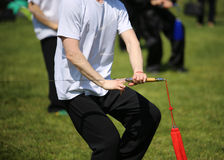 Tai Chi martial arts athlete makes motions with sword Royalty Free Stock Images