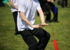 Tai Chi martial arts athlete makes motions with sword. Tai Chi martial arts athlete expert makes motions with sharp sword Royalty Free Stock Images