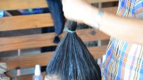 Tai Dam folk som gör den svarta Tai-frisyren för frisyr och för smink lager videofilmer