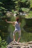 TAI-Qui praticando de .oman na frente de um rio. Fotos de Stock Royalty Free