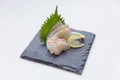 Tai Sashimi: Skivade rå Tai Red Seabeam Fish Served med den skivade rädisan på stenplattan arkivfoto