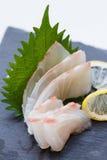 Tai Sashimi : Sliced Raw Tai Red Seabeam Fish Served with Sliced Radish on Stone Plate.  Royalty Free Stock Photography