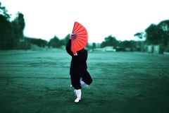 Taichi wushu master woman in the Outdoors move with the fan stock images