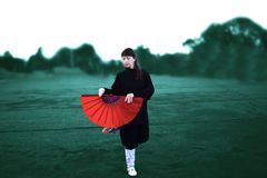 Taichi wushu master woman in the Outdoors move with the fan stock photo