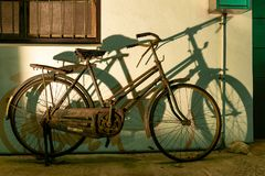 TAICHUNG, ТАЙВАНЬ 31-May-2018 Старый заржаветый велосипед и своя тень против стены стоковое изображение rf