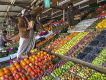 Arab men sells fresh fruits at a fruit market in Taif, Makkah, Saudi Arabia. TAIF, SAUDI ARABIA-JANUARY 22, 2018 : Unidentified Arab men sells fresh fruits at a stock photos