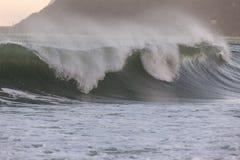 Taifun bewegt mit Spray gegen Sonnenuntergangorange wellenartig Lizenzfreies Stockfoto