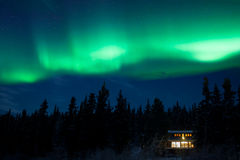 Taiga home under Northern Lights Aurora borealis Royalty Free Stock Photo