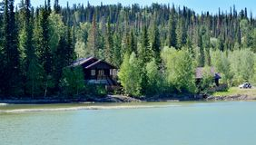 Taiga house near the lake stock photo