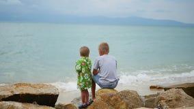 tailândia As crianças sentam-se no litoral e olham-se para fora na distância vídeos de arquivo