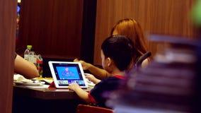 Tailândia, Banguecoque, o 23 de novembro de 2015 A família asiática que janta em um restaurante, a criança usa uma tabuleta 3840x vídeos de arquivo
