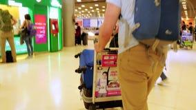Tailândia, Banguecoque, o 22 de novembro de 2015 Homem novo com a bagagem que sae no aeroporto 3840x2160 vídeos de arquivo