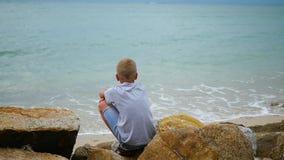 tailândia a criança senta-se no litoral e olha-se para fora na distância vídeos de arquivo