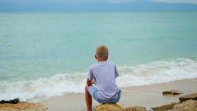 tailândia a criança senta-se no litoral e olha-se para fora na distância filme