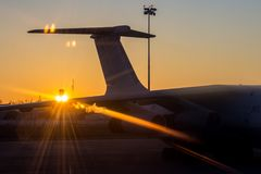 The tail of the aircraft on the background of the rising sun. This photo was taken early in the morning at Sheremetyevo airport. The moment when the sun rising Stock Photo