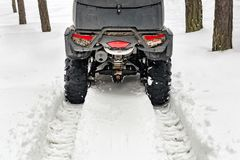 Tail of ATV 4wd quad bike in forest at winter. 4wd all-terreain vehicle stand in heavy snow with deep wheel track. Seasonal royalty free stock photography