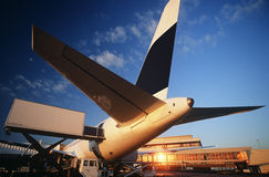 Tail fin of airplane at airport sunset Stock Photo