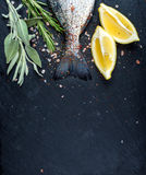 Tail of fresh raw Dorado or sea bream fish on black slate stone board with spices, herbs, lemon and salt Stock Photo