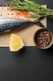 Tail of fresh raw mackerel. With spice on black background, top view Stock Photos