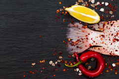 Tail of fresh raw red tilapia fish on black slate stone board with spices, chili pepper, lemon and pink salt. Culinary seafood background. Top view, copy space Stock Photos