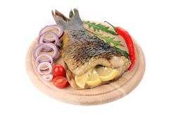 The tail of fried fish on a wooden plate Royalty Free Stock Photography