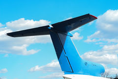 Tail of a jet airplane in front of sky background with flying airplane track, bottom view.  Royalty Free Stock Photos
