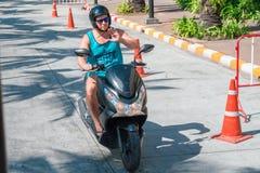 TAILÂNDIA, PHUKET, o 22 de março de 2018 - o indivíduo monta um 'trotinette' na rua e acena sua mão ao fotógrafo fotos de stock