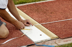Tail of the Tape. An official measures  the distance in the long jump event during a college track meet Stock Image