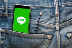 TAILANDIA - 13 de julio - Smartphone que abre la medios línea social uso en la pantalla, en bolsillo de la mezclilla del jenim co Fotos de archivo libres de regalías