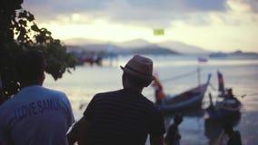Tailandia, Koh Samui, el 28 de diciembre de 2015 Dos hombres de los viajeros que miran el cielo nublado colorido de la puesta del almacen de metraje de vídeo