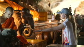 Tailandia, Phuket - 19 de febrero de 2017: Templo de la cueva con un Buda de mentira Wat Suwan Khuha El monje conduce el ritual almacen de video