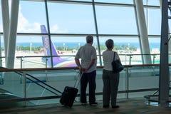 Tailandia, Phuket - 09 05 18 Hombre envejecido y mujer de dos personas así como la espera de la situación del equipaje en el aero fotografía de archivo