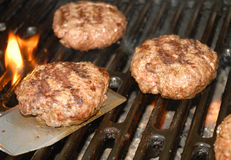 Tailgate grilling hamburger time. Hamburgers grilling on the grill with the spatula holding one of the burgers Stock Image