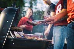 Tailgating: Άτομο που ψήνει τα λουκάνικα και άλλα τρόφιμα για Tailgate PA στη σχάρα Στοκ Εικόνες