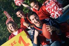 Tailgating: Aufgeregte Fans, die für Team And Holding Sign zujubeln Stockbild