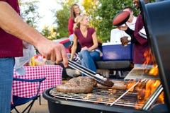 Tailgating: Bratwurst o salsiccia sulla griglia al cofano party Fotografie Stock Libere da Diritti