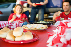 Tailgating: Focus On Apple Pie On Table Of Tailgate Party Food. Group of friends doing football tailgating.  Cooking food, cheering, etc Stock Image