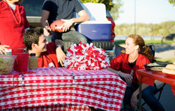 Tailgating: Focus On Empty Area On Picnic Table. Group of friends at a football tailgating party outside Stock Image