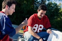 Tailgating: Guy Friends Having Some Drinks Before Game. Group of friends doing football tailgating.  Cooking food, cheering, etc Royalty Free Stock Image
