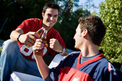 Tailgating: Guys Toasting Their Team Before Game. Group of friends doing football tailgating.  Cooking food, cheering, etc Royalty Free Stock Images