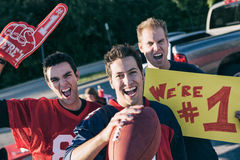 Tailgating: Male Football Fans Excited For Game. Group of friends at a football tailgating party outside Stock Image