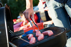 Tailgating: Man Grilling Sausages On Charcoal Grill For Party Stock Images