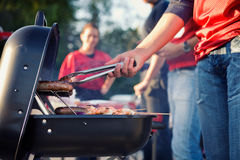 Tailgating: Man som grillar korvar och annan mat för bakluckaPA royaltyfria bilder