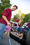 Tailgating: Man Working The Grill At Tailgate Party. Series with college football fans tailgating and having fun before the game royalty free stock photo