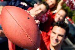 Tailgating: Mannen rymmer fotboll ut till kameran fotografering för bildbyråer