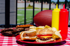 Tailgating Meal. With cheeseburger, hot dog, potato chips, hamburger patties, hot dog wieners, mustard and ketchup bottles, and American football.  Football Stock Image