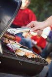 Tailgating: Uomo che griglia le salsiccie e l'altro alimento per PA della porta posteriore immagini stock