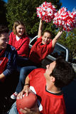 Tailgating: Woman Cheers While Holding Poms In Air. Group of friends at a football tailgating party outside Stock Images