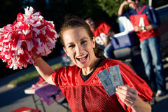 Tailgating: Woman Holding Pair Of Tickets To Football Game. Group of friends doing football tailgating. Cooking food, cheering, etc royalty free stock photos