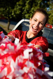 Tailgating: Woman Holding Poms Cheers For Team. Group of friends doing football tailgating.  Cooking food, cheering, etc Stock Photo